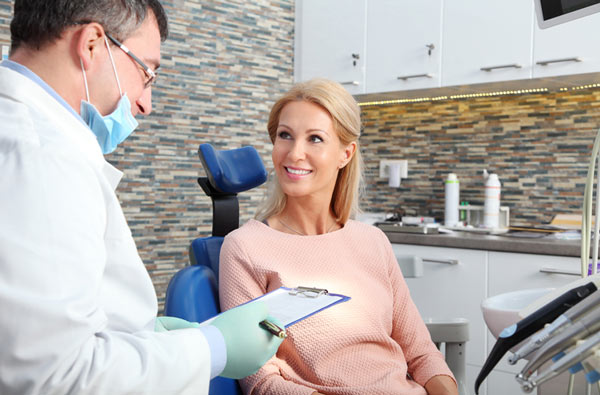 Woman talking to dentist during dental exam